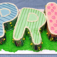 Celebrate Spring Cake created using individual letters to spell out APRIL. Each letter is a different flavor/filling combo. All covered in buttercream.