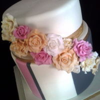 Deep 2 Tier Wedding Cake With Sugar Roses Unusual and striking wedding cake with a mixture of pink, grey and gold.