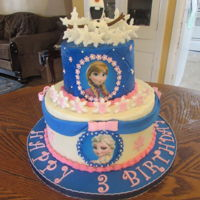 Frozen Elsa And Anna Chocolate cake frosted with buttercream. All decorations are fondant. The images are ediible sugar sheets.