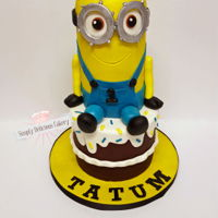 Minion 1St Birthday 4in round minion on top of a 6in round cake covered in chocolate ganache. Fondant detail.