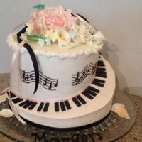 Piano Birthday Cake A carved 2 tiered cake covered in buttercream with fondant keyboard and stenciled musical score, topped with gum paste peony and lilies.