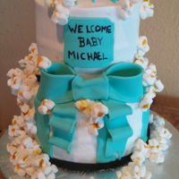 Popcorn Baby Shower Vanilla cream cake with butter cream. Popcorn is made mini marshmallows and ribbon is fondant.