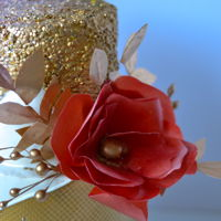 Red Wafer Paper Cake covered in fondant and decorated with gold sequence and mock smocking patterns with wafer paper flowers and gold wafer paper leaves....