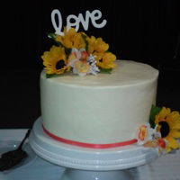 Sunflower And Coral Cake All buttercream with sunflowers and coral flowers and ribbon.