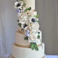 Woodland Beauty An ivory wedding cake with a fresh floral cascade of anemones, blush roses and lots of foliage