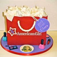 American Girl Gift Bag Cake Red modeling chocolate covering the gift bag. Fondant makeup, gumpaste handle and tissue paper, edible images for tag and decorations.