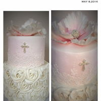Bella's 1St Communion Two tier cake with gumpaste fantasy poppy and dogwood flowers. Cake lace around the top tier and buttercream rosettes on botton tier. The...