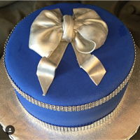 Blue And Silver Cake Dark chocolate velvet cake, covered in gamache, then covered with blue fondant. Fondant, hand painted bow.