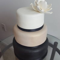 Champagne Magnolia Cake 3 Tier wedding cake, black, champagne and white marshmallow fondant tiers. Middle tier is champagne tinted fondant painted with a gold...