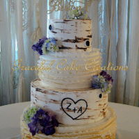 Elegant Rustic Birch Bark Wedding Cake Elegant Rustic Birch Bark Wedding Cake with a Fondant Ombre Ruffle Design accented with Fresh Purple, Blue and Green Hydrangea