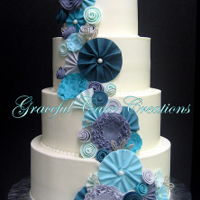 Elegant White Wedding Cake With Whimsical Fondant Flowers Elegant White Wedding Cake with Whimsical Fondant Flowers in Shades of Teal and Grey