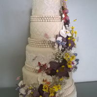 Orchids And Lace A 5 tier wedding cake with an orchid cascade made entirely of gumpaste oncidiums, Phalenopsis, dendrobiums and stephanotis