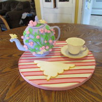 Rosey Teapot Ribbon fondant roses, gumpaste/fondant 50/50 handle and spout. Piece of styrofoamfor base