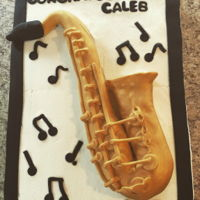 "Saxophone Cake Saxophone made out of fondant, then sprayed with gold spray. Cake is a WASC 12""x18""x4""."