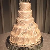 Wedding Cake That Matches Dress 5-tiered cake designed to drape like the wedding dress. Enhanced by pieces of cake jewelry and monogrammed topper. All covered in pearlized...