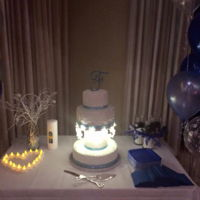 Winter Wedding Cake Buttercream covered cake with royal icing and poured sugar snowflakes. led seed lights light up the sugar snowflakes.
