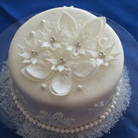 Winter Wonderland  2 tier mini almond sour cream cake with butter cream icing covered with fondant. Sugar paste flowers and snowflakes. Wilton sugar pearls....