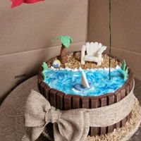 A Day At The Beach For Father's Day vanilla cake filled with cream cheese filling, butter cream iced with kit kats on the sides. All props are hand made and edible except the...