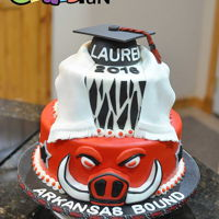 "Arkansas Razorback Graduation Cake 2 tier cake 10"" and 6"" tiers. Grad hat formed with RKT and covered with MMF. Cake covered and decorated with MMF."