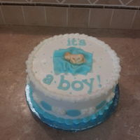 "Baby Shower Cake ""it's A Boy"" 9"" chocolate cake with a baby on top made of gumpaste and fondant laying on a fondant blanket."