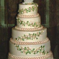 Blossoms, Vines And Pearls White textured buttercream with fondant ivory pearl borders. Gumpaste ivory blossoms with pearl centers and gumpaste leaves are used to...