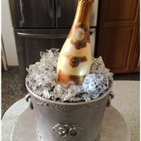 Champagne Bottle In Ice Bucket Ice bucket was pink champagne cake with pink champagne buttercream. Ice made from isomalt, lit up with LED lights. Champagne bottle made...