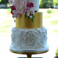 Golden Wedding Cake Ruffles, sugar flowers and gold luster wedding cake.