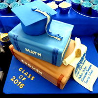 Graduation 2016  Three tiered book and cap cake covered in fondant and cupcakes. Our school goes from kindergarten to 12th grade so the entire graduating...