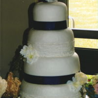Navy And White With Rustic Accent White buttercream with navy ribbon borders and rustic buttercream accent on two tiers.