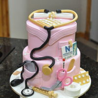 Pink Nursing Graduate Cake 2 tier cake resembling Pink nursing scrubs. Graduate was an honor student so stethoscope, syringe and pill packs were colored gold. Blood...