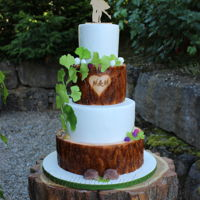 Rustic Weddingcake A rustic wedding cake with tree disc and gingko leafes with a dancing couple on top.