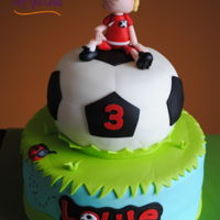 Soccer Fan This is a two tier covered in fondant with fondant accents. The soccer player, on top, is handmade from fondant. Thanks for looking!