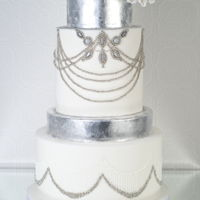 Vintage Jewels This vintage inspired white and silver jewelled wedding cake features hundreds of tiny sliver drags placed on one at a time along with...