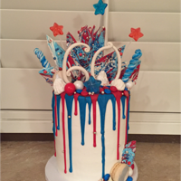 Birthday & 4Th Of July Drip Cake White chocolate drip over buttercream with lots of treats on top for a 60th birthday and 4th of July celebration.