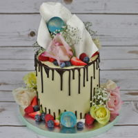 Birthday Cake White chocolate ganache covered cake. Fresh flowers, berries, dark and white chocolate decorations.