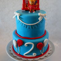 Daniel Tiger Cake  Eight and Six inch rounds covered in fondant with souvenir Daniel Tiger and Trolley on top. Design inspiration from Sweetly Chic Cake...
