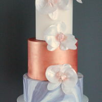 Marble, Metallics And Moth Orchids Marble fondant with copper bronze hand painted middle tier with wafer paper moth orchids.