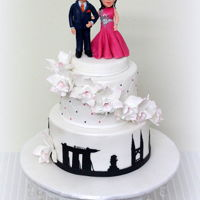 Personalised Engagement Cake The Engagement Cake was personalised with the couples figurine dressed in their party costumes. The middle tier was decorated with Orchid...