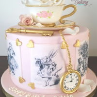 Vintage Alice In Wonderland Cake Vintage Alice in Wonderland themed cake with vintage edible images, a sugar tea cup, saucer, key and watch.