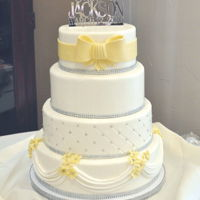 White And Yellow Wedding Cake 4 tier white and yellow wedding cake. Marshmallow fondant, silver dragees and rhinestones with fondant bow.
