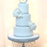 White Bling Wedding Cake The Three Tier White Bling Wedding Cake was designed with White damask on the top and bottom tiers and quilted design with tiny silver...