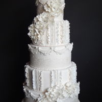 Frills And Fancy 5 tier wedding cake inspired by vintage weddings. Ruffles, edible lace, pearls and abstract sugar flowers