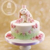 Lilah's Little White Bunny Cake Classic Vanilla sponge cake with strawberry jam and vanilla buttercream filling, handmade bunny rabbit topper and handmade sugar flowers