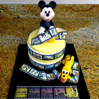 Mickey And Pluto Birthday Cake  Fondant covered lemon pound cake with Mango filling and coconut buttercream icing. Mickey and Pluto are fondant and film strips are edible...