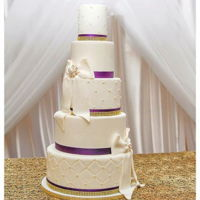 Royal Wedding Cake The colors of royalty are reflected on this cake as gold and purple with bows are the decor.