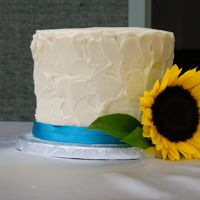 Small Sunflower   Six inch round in textured buttercream with Satin ribbon and fresh Sunflower.