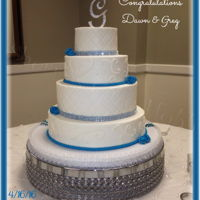 4 Tier Buttercream Wedding Cake Iced in smooth buttercream with diamond pattern, scroll work, fondant decorations and bling. New Orleans themed cake pulls. Accent color to...