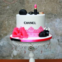 Chanel Chanel themed cake i made yesterday,handbags and some cosmetics made from fondant,edible lace and some pink bow to finish up the look.