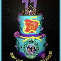 Disney Descendants Buttercream Birthday Cake Iced in smooth buttercream with fondant decorations and licensed Disney cake accessories. Multicolored buttercream, ribbon roses and piped...
