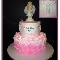 First Communion Precious Moments Cake Water color smooth buttercream with fondant decorations and a precious moments cake topper and rosettes on the bottom.
